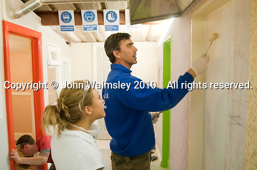 Painting & Decorating student watches an instructor apply paint with a roller, Able Skills, Dartford, Kent.