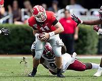 ATHENS, GA - OCTOBER 12: Kobe Smith #95 of the South Carolina Gamecocks attempts to tackle quarterback Jake Fromm #11 of the Georgia Bulldogs during a game between University of South Carolina Gamecocks and University of Georgia Bulldogs at Sanford Stadium on October 12, 2019 in Athens, Georgia.