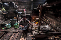 Dafrin Ambotang (35) sits by the fire in his home in the Bajau stilt village of Pulo Papan. Ambotang is recognised as one of the best divers in the village, able to stay down for up to four minutes on one breath.