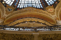 "Central ""Belle Epoque"" coupole in Les Galleries Lafayettes department store.  Stained glass, coupole, guilded arches with wood carvings.  Balconies for each of the upper floors are visible.  Photo shot from the ground floor looking up."