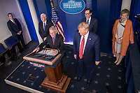 United States President Donald J. Trump stands as Director of the National Institute of Allergy and Infectious Diseases at the National Institutes of Health Dr. Anthony Fauci  delivers remarks on the COVID-19 (Coronavirus) pandemic in the Brady Press Briefing Room at the White House in Washington, DC, March 25, 2020, in Washington, D.C. Members of the Coronavirus Task Force including US Vice President Mike Pence; US Secretary of the Treasury Steven T. Mnuchin; and Dr. Deborah L. Birx, White House Coronavirus Response Coordinator stand behind the President and listen.<br /> Credit: Sarah Silbiger / Pool via CNP/AdMedia
