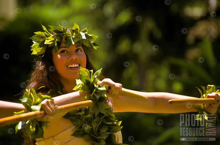 Hula (kahiko) dancer with two kalaau sticks and wearing maile (leaf) lei, Lei Day celebration at Hilton Hawaiian Village Hotel