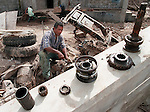 Pablo Matute salvages auto parts from a Toyota  buried by mud from flood waters created by Hurricane Mitch in the Honduran capital of Tegucigalpa on Monday, December 7, 1998. Photo by Christopher Evans