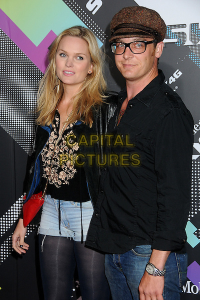 SUNNY MABREY & ETHAN EMBRY.The T-Mobile Sidekick 4G Launch Party held at a private lot in Beverly Hills, California, USA..April 20th 2011.half length shirt black glasses shirt brown cap hat tattoo denim shorts arm around tights married husband wife .CAP/ADM/BP.©Byron Purvis/AdMedia/Capital Pictures.