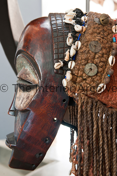Profile view of a Congo mask Mbagani, part of a large collection displayed throughout the house