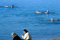 Jordan. Dead sea. Jordanians tourists (muslim men) take a bath, swimm and float on the salt water. They enjoy themselves on a sunny friday afternoon. Friday is the day off (resting day) in the arabian culture. Women are seated on the  seaside and wear veils on their head as part of muslim tradition and religion. On the other side of the sea is Palestine and the West Bank (Occupied Territories by Israel). © 2002 Didier Ruef