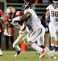 TALLAHASSEE, FL 11/19/11-FSU-UVA111911 CH-Florida State's Bert Reed is grabbed by Virginia's Corey Mosley  during first half action Saturday at Doak Campbell Stadium in Tallahassee. .COLIN HACKLEY PHOTO