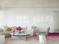 The luxurious penthouse apartment is full of edgy chic and sizzling colour. The 1970s curved sofa us by Milo Baughman, and the custom-made silk shag rug is by Beauvais Carpets.