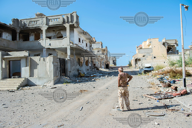 A member of a de-mining team looks over an area of destroyed buildings being cleared after it was recently re-taken from ISIS.
