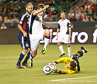 CARSON, CA – APRIL 30, 2011: Chivas USA goalie Dan Kennedy (1) deflects the ball from New England Revolution midfielder Zak Boggs (33) during the match between Chivas USA and New England Revolution at the Home Depot Center, April 30, 2011 in Carson, California. Final score Chivas USA 3, New England Revolution 0.