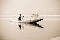 Toned black and white photograph of traditional Kashmiri shikara and paddler at sunrise, Dal Lake, Srinagar, Kashmir, India.