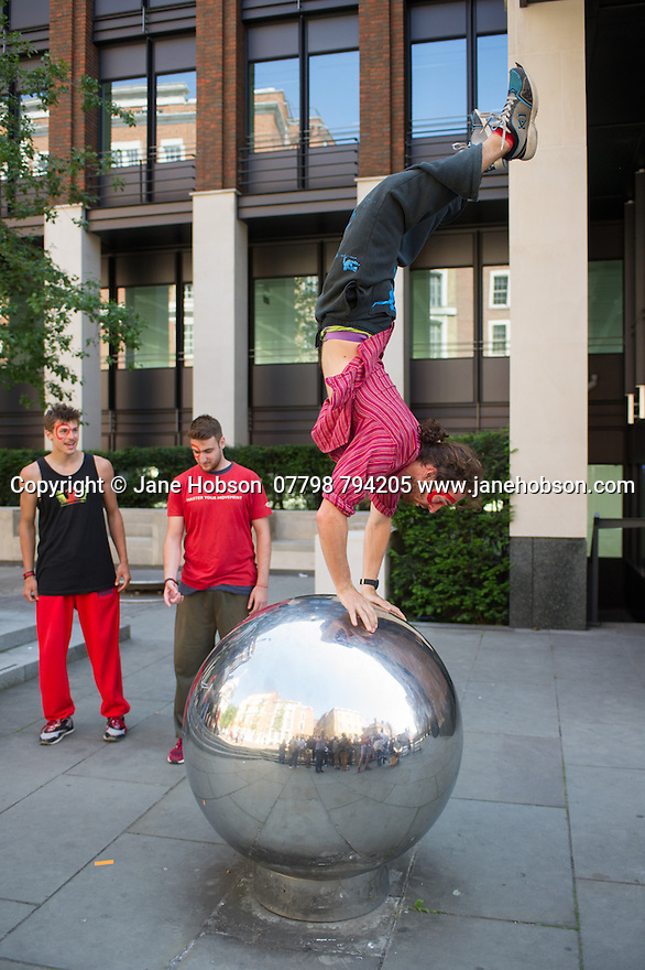 London, UK. 21.06.2014. Belarus Free Theatre, in conjunction with Parkour Generations, stage a protest event, to coincide with their production of RED FOREST at the Young Vic theatre. After the explosion at Chernobyl in 1986, the forest turned red. The event was to highlight that air and water supplies today are under attack from dangerous and dirty forms of energy production. Picture shows: Jacob Peregrine-Wheller at the north side of the Millenium Bridge. Photograph © Jane Hobson.