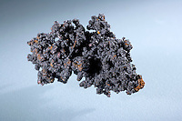 TENORITE ON COPPER<br /> Copper Oxide (CuO), A Secondary Copper Mineral<br /> Thin coating of Tenorite on micro Cuprite octahedrons on native Copper. Also known  as black copper oxide, melanconite and melanochalcite. Monoclinic, prismatic crystal.