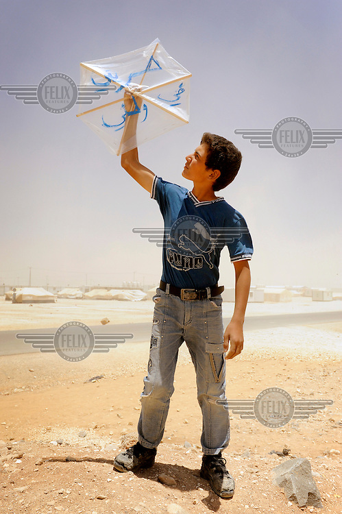 Syrian refugee Khaled holds up a kite he has made himself. On it he has written his personal message of peace for his country. 'We left Syria because we didn't have freedom anymore' explained Khaled who has been forced to leave Syria four months ago to become a refugee in the camp. He wanted to write his dream on his kite and wrote 'I want my freedom in my land'. When asked to tell his personal opinion of freedom Khaled said 'Freedom to me is to be able to run, play, and go places without being afraid.' /Felix Features