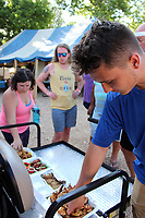 MEGAN DAVIS/MCDONALD COUNTY PRESS Gary Winthorpe (right) of Miami, Okla. wasted no time before sinking his teeth into the chicken wing contest entries. Winthorpe and five others were chosen to judge the grilled goods at the 2019 Chicken Coop Open on Saturday.