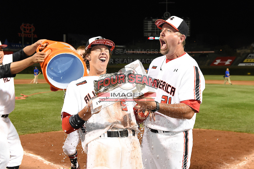 Ryan Mountcastle (5) and coach Sean Casey (21) react to having the water bucket dumped over their heads by Sati Santa Cruz and Kody Clemens (hidden) at the MVP award presentation after the Under Armour All-American Game on August 16, 2014 at Wrigley Field in Chicago, Illinois. (Mike Janes/Four Seam Images)