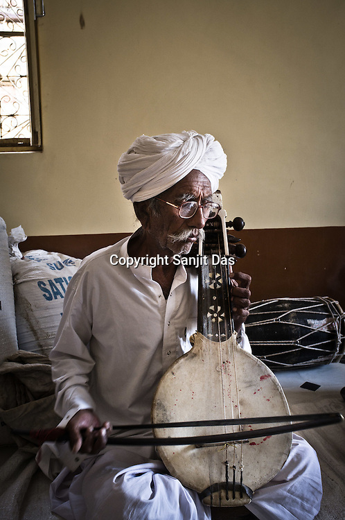 75-year-old Manganiyar artist, Saqar Khan plays his Kamancha (music instrument) inside his house in Hamira village of Jaiselmer district in Rajasthan, India. Photo: Sanjit Das/Panos