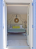 The French windows are flung wide allowing a view of the elaborate wrought-iron four poster bed in this guest bedroom