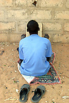 A talibe learning coranic versets outside the house of the marabout in Maradi, Niger. In Niger, coranic schools still exist and are very traditional. Talibe, pupils, even go and beg for money and food in the afternoon in order to pay the marabout.