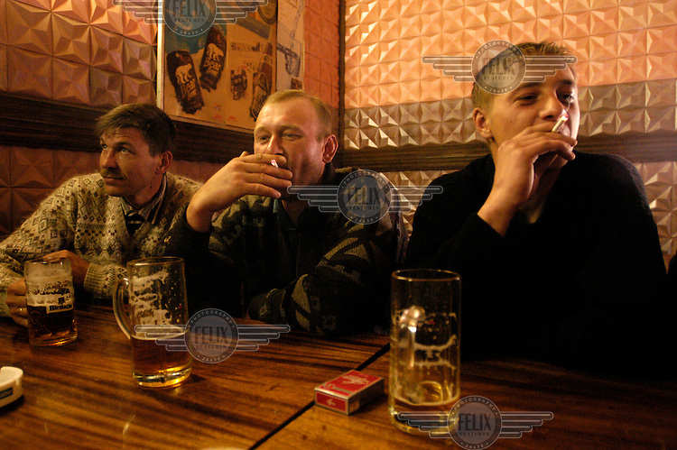 Lithuanian Poles, living in the small town of Ejszyszki near the Belorussian border, drink beer and smoke in a pub. From left to right, Slawek, Denis and Miroslaw.