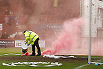 Stewards dousing the smoke bombs with sand