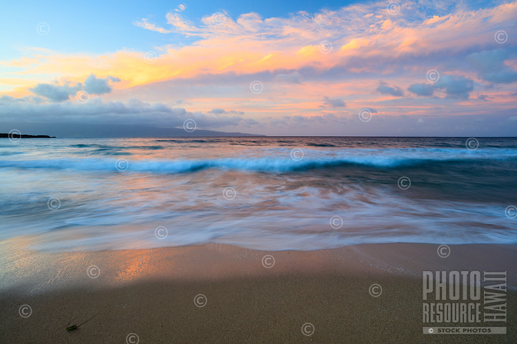 Maui Symmetry: A line of fluffy golden-pink clouds spreads across the sky while the surf below falls in similar shape and softness of appearance at DT Fleming Beach Park, Kapalua, Maui.