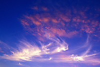 Blue sky with pink and white swirly clouds