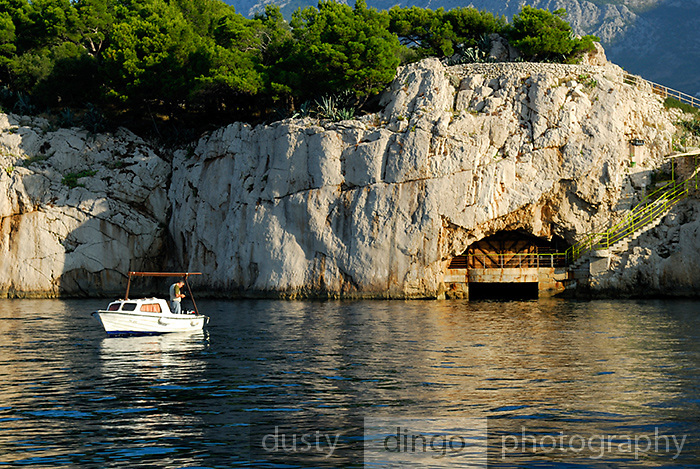 Small boat with fisherman, anchored off rocky cliff. In summer the fenced off cave is used as a disco nightclub. Makarska, Croatia