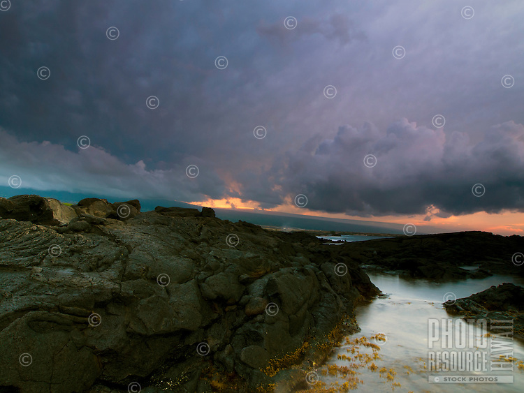 Beyond Keahole Point and storm clouds, the last light of the sunset highlights the snow on Mauna Loa, Big Island.