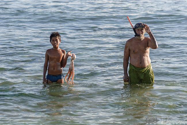 Father and son fishing off the beach in Kiritimati in Kiribati.
