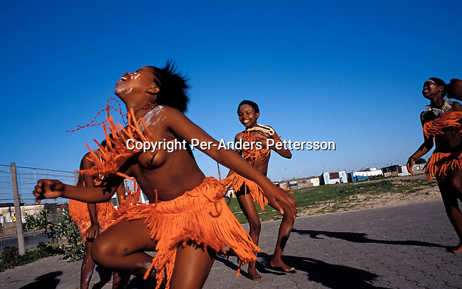 didance00024 .Unidentified girls dancing traditional Xhosa dances in the school yard on August 22, 2001 in Site B Khayelitsha, a township about 35 kilometers outside Cape Town, South Africa. They are part of Siyazama aftercare center for abused children in their school. Many children are abused sexually or physically in their homes and neighborhood. Khayelitsha is one of the poorest and fastest growing townships in South Africa. People usually come from the rural areas in Eastern Cape province to find work as maids and laborers. Most people don't find work and the unemployment rate is very high, together with lot of violence and a growing HIV-Aids epidemic itÕs a harsh area to live in..©Per-Anders Pettersson/iAfrika Photos.