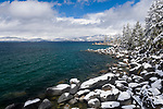 Lake Tahoe and snow covered boulders and coves during a clearing winter storm