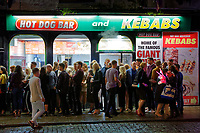 Revellers queue outside a kebab take away in Wind Street, Swansea, Wales  on Mad Friday, Booze Black Friday or Black Eye Friday, the last Friday night before Christmas Day, when traditionally people in the UK go out to celebrate the start of their holidays. Friday 22 December 2017