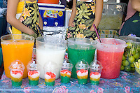 Hmong teenagers serving an array of multicolored fruit drinks. Hmong Sports Festival McMurray Field St Paul Minnesota USA