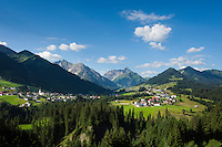 Austria, Vorarlberg, Kleinwalsertal, Riezlern: with parish church Virgin Mary Sacrifice, at background Allgaeu Alps and summit Widderstein | Oesterreich, Vorarlberg, Kleinwalsertal, Riezlern: Dorf mit Pfarrkirche Mariae Opferung, im Hintergrund die Allgaeuer Alpen mit dem Widderstein