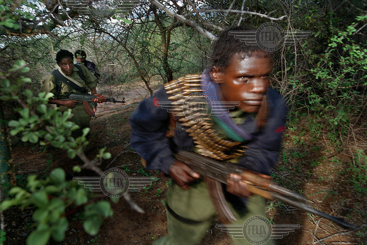 Oromo Liberation Front (OLF) fighters patrol an area of bush near the Kenyan border, in their ?4th Military Zone?. The area is dangerous and the fighters need to keep a look-out for both Ethiopian government forces and Kenyan border patrols. Kadjila (front) is 27, and was once in the Ethiopian army but defected to join the OLF. .The OLF have been fighting a ?forgotten war? against successive Ethiopian governments since the 1970s. Their aim is independence for Oromia and its 30 million strong Oromo community.