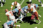 Washington Redskins offensive right tackle Mark May (73) opens a hole for running back George Rogers (38) as he carries the ball during the first quarter of game against the Houston Oilers at RFK Stadium in Washington, DC on September 16, 1985.   Rogers ran for 31 yards and a touchdown on the play.  The Redskins won the game 16 - 13.<br /> Credit: Howard L. Sachs / CNP
