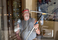 NWA Democrat-Gazette/J.T. WAMPLER Jim Lumley of Rogers cleans a window Wednesday Sept. 2, 2015 at a business in downtown Rogers. Lumley works for Donahey Window Washers and has several clients in the downtown area.
