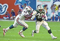 Curtis Martin carries the ball as Daryl Gardener gives chase as the Jets defeated the Dolphins 20-3 in Miami , FL on November 19, 2000. (Photo by Brian Cleary / www.bcpix.com)