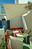 The simple awning provides welcome shade for the seating area on the second floor terrace