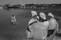 A young member of Mt. Calvary Missionary Baptist Church is comforted by her father as she prepares to be baptized in Skull Creek on Hilton Head Island. Mt. Calvary is one of the few churches on Hilton Head Island that still performs traditional river baptisms. Other churches have given up the practice as development has limited their access to the island's waterways.