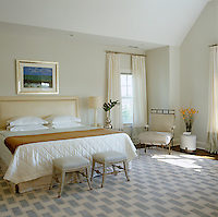 In the master bedroom a small blue seascape sings against the muted colour of the walls and its tones are subtly picked out in the rectangles of a Tibetan rug on the floor