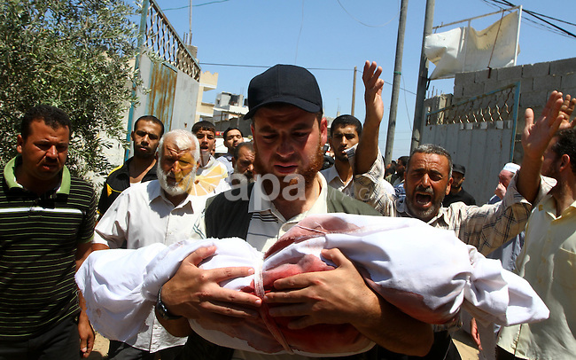 A Palestinian man carries the body of two-year-old boy Malek Sha'at during his funeral in Rafah in the southern Gaza Strip August 19, 2011. An Israeli air strike killed the leader of an armed Palestinian faction, a top lieutenant, three other members and Sha'at in the southern Gaza Strip on Thursday, the group said, hours after Israel blamed gunmen from the territory for cross-border attacks. Photo by Ashraf Amra