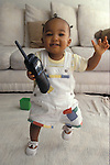 Richmond, CA  African American baby twelve months old just starting to walk, carrying mother's telephone  MR
