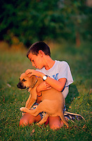 A young boy holds a puppy in a grassy meadow.