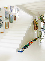 A row of flip flops in every conceivable colour lines the burnt concrete staircase in the entrance hall