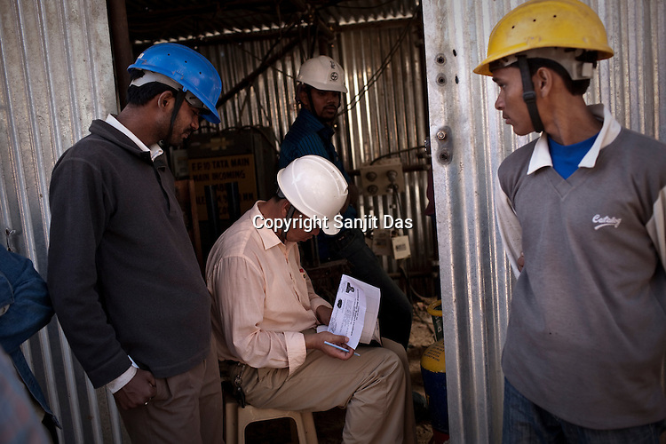 Chinese engineer from Sepco is seen with Indian workers at the construction site of the Adani Power plant of 4620 MW capacity in Mundra port industrial city of Gujarat, India. Indian power companies have handed out dozens of major contracts to Chinese firms since 2008. Adani Power Ltd have built elaborate Chinatowns to accommodate Chinese workers, complete with Chinese chefs, ping pong tables and Chinese television. Chinese companies now supply equipment for about 25% of the 80,000 megawatts in new capacity.