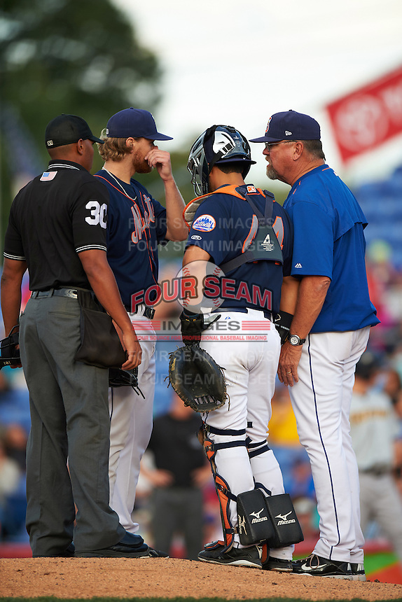 Binghamton Mets pitching coach Glenn Abbott (55) talks with pitcher Matt Koch (20) as umpire Jeremie Rehak and catcher Xorge Carrillo (44) listen in during a game against the Trenton Thunder on August 8, 2015 at NYSEG Stadium in Binghamton, New York.  Trenton defeated Binghamton 4-2.  (Mike Janes/Four Seam Images)