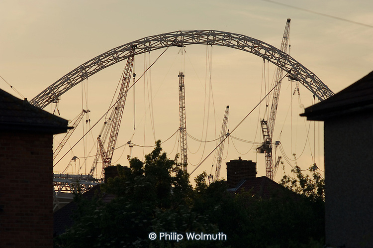 The steel arch of the partially completed roof of the new Wembley National Stadium in North London, seen from the neighbouring St.Raphael's Estate.