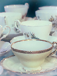 Antique tea cups sit on a table.